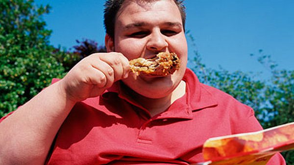 мужчина ест жирную пищу